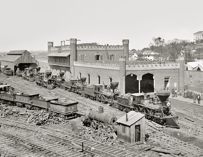 A steam locomotive and cars sits in front of brick building.