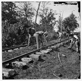 Black soldiers repairing a railroad track.