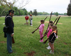 A Union soldier watches as children practice a musket drill.