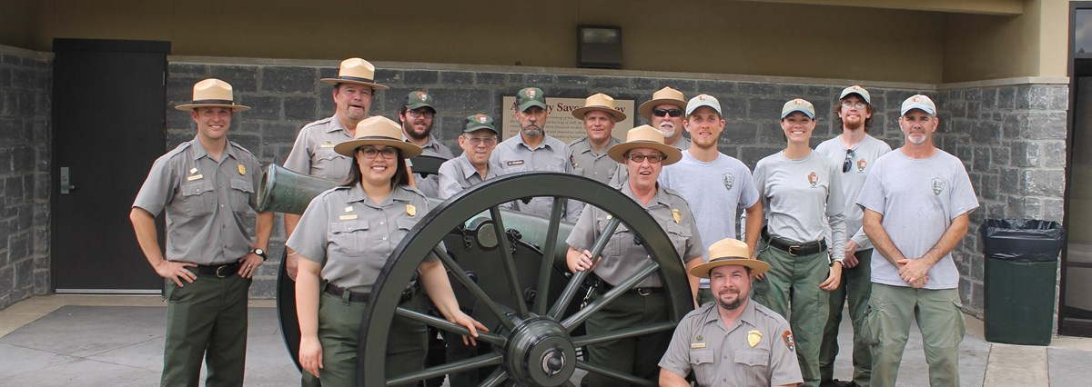 Park Rangers stand around a cannon