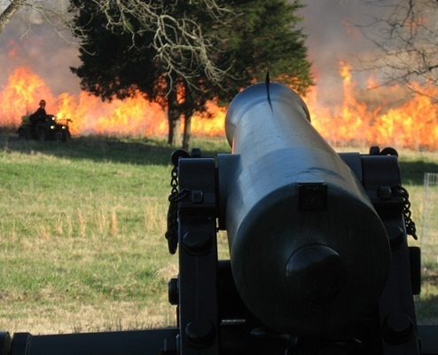 Fire burns in front of a cannon.