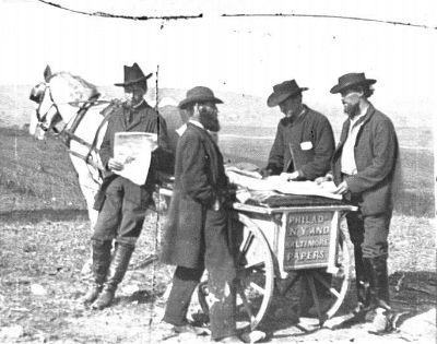 Four men standing at a horse drawn newspaper cart