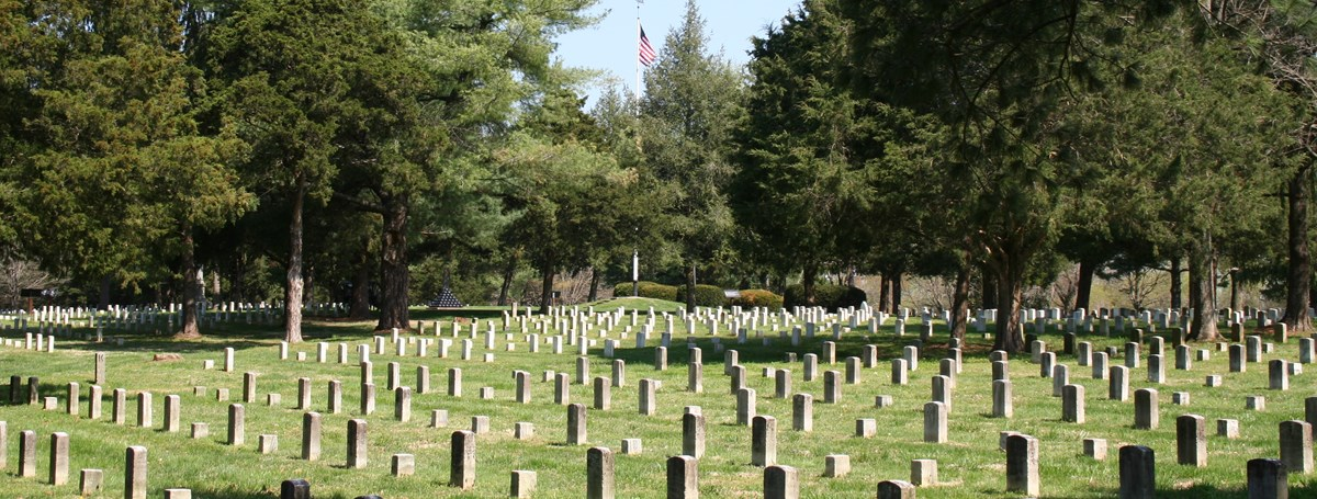 A white flagpole with an American Flag flies over a cemetery with rows of white headstones.