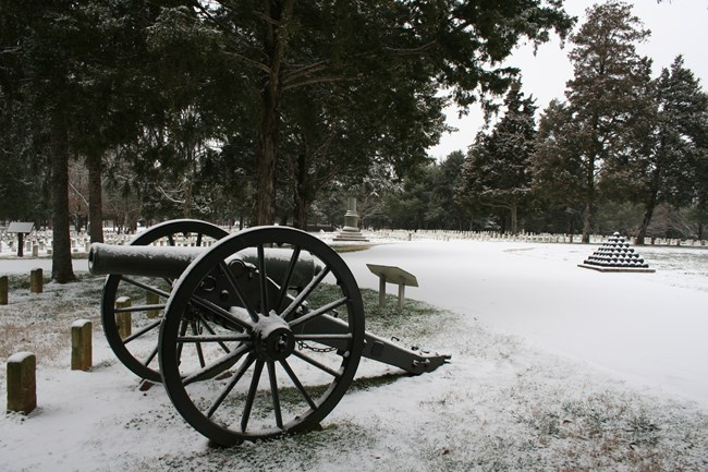 A Civil War cannon sits in a National Cemetery covered in snow, with a pyramid of black cannon balls in the background.