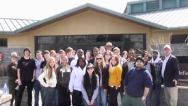 Group of students and rangers in front of the park visitor center.
