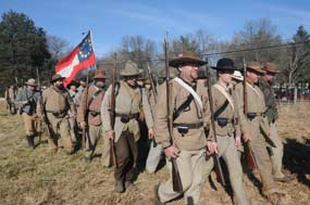 Confederate soldiers march while carrying a first national flag.