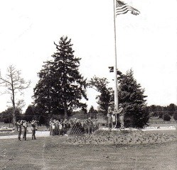 Black and white photo of boy scouts performing a flag ceremony at a flag pole.