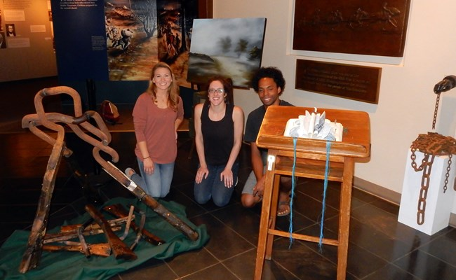 Three college students pose knelling in the midst of paintings and sculptures they created.