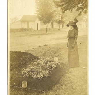 Historic photo of a woman standing next to grave in Evergreen Cemetery.
