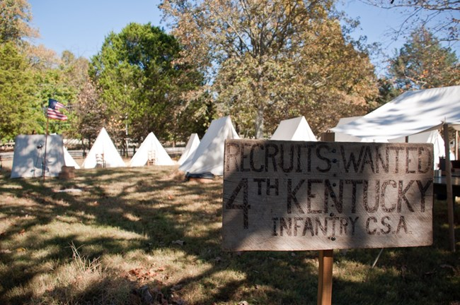 "A wooden sign reading ""Recruits Wanted 4th Kentucky Infantry, CSA"" stands in front of a row of tents."