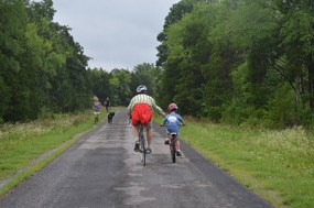 Bicyclists pass joggers on the park tour road.