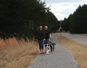 A couple walks their dogs on a gravel trail.