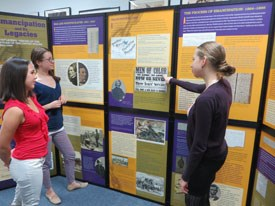 Three young women look at exhibit panels.