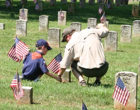 A cubscout and his father place American flags in front of headstones.