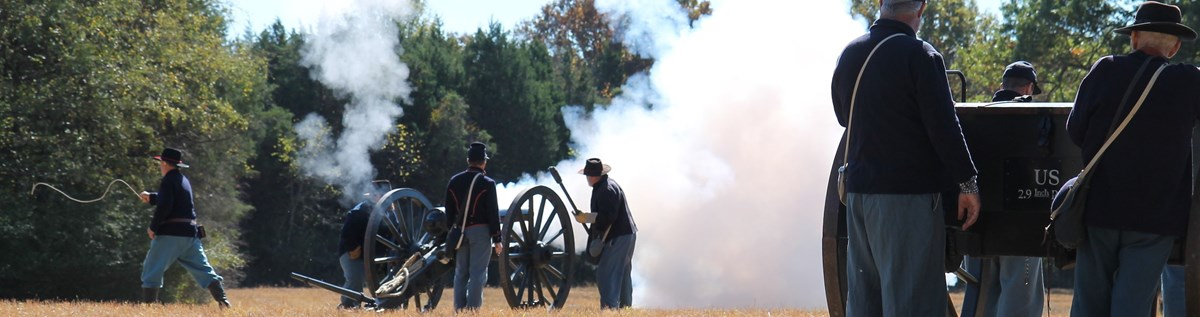 Union soldiers fire a cannon while other soldiers look on.