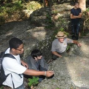A park ranger and high school students crouch behing limestone boulders in the Slaughter Pen.