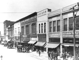 1925 photo of Murfreesboro's town square shows cars parked along the street and people walking along the sidewalks in front of businesses.
