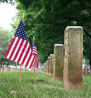 American flags placed in the ground in front of a row of headstones.