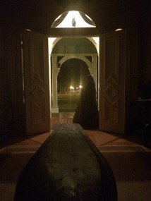 A woman dressed for mourning stands inside the open front door of Oaklands Mansion