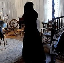 A women in a black mourning dress stands in a room in the Sam Davis Home.