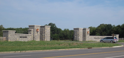 A car enters the park through the stone pillars of the main gate.