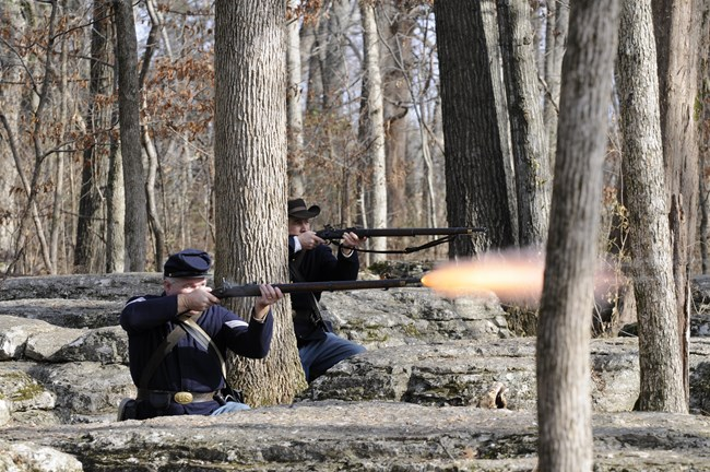 Two Union soldiers fire muskets behind rock outcroppings
