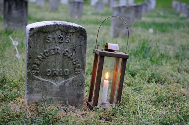 A candle lantern sits next to the national cemetery headstone of Spencer Sober. The stone reads 5723 - Spencer Saber - Ohio.