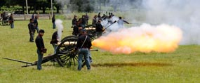 A large ball of orange flame shoots out of a Civil War cannon.