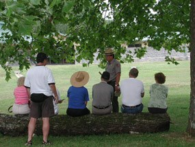 A park ranger talks to visitors sitting on a log.