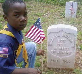 A cub scout places a flag at soldier's grave site.