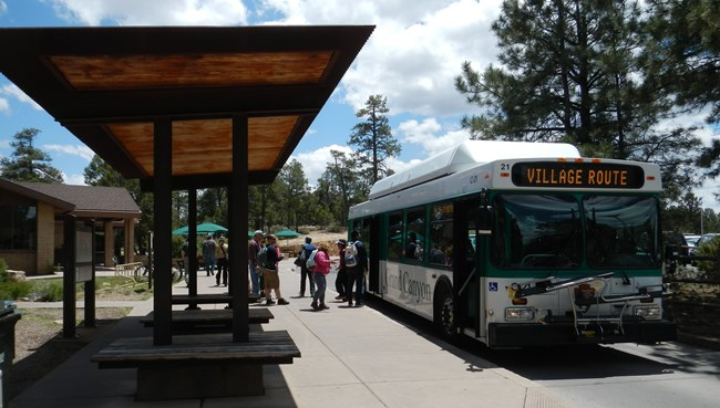 Photo of park visitors preparing to board a shuttle bus at Grand Canyon National Park, Arizona.