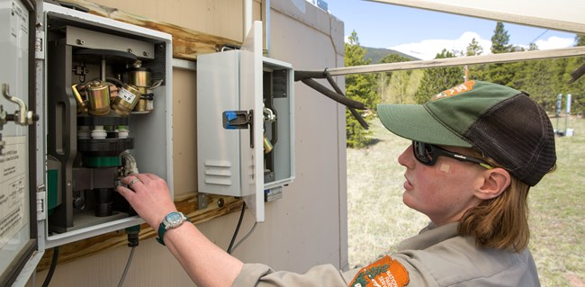 An NPS employee looking at outdoor air monitoring equipment