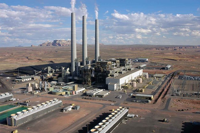 Photo of Navajo Generating Station, a large power plant with three towering smokestacks in the desert.