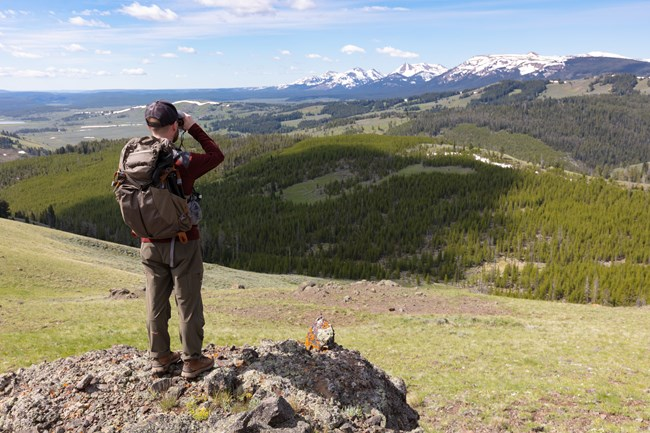 Man in hiking attire looking at distant mountains with binoculars