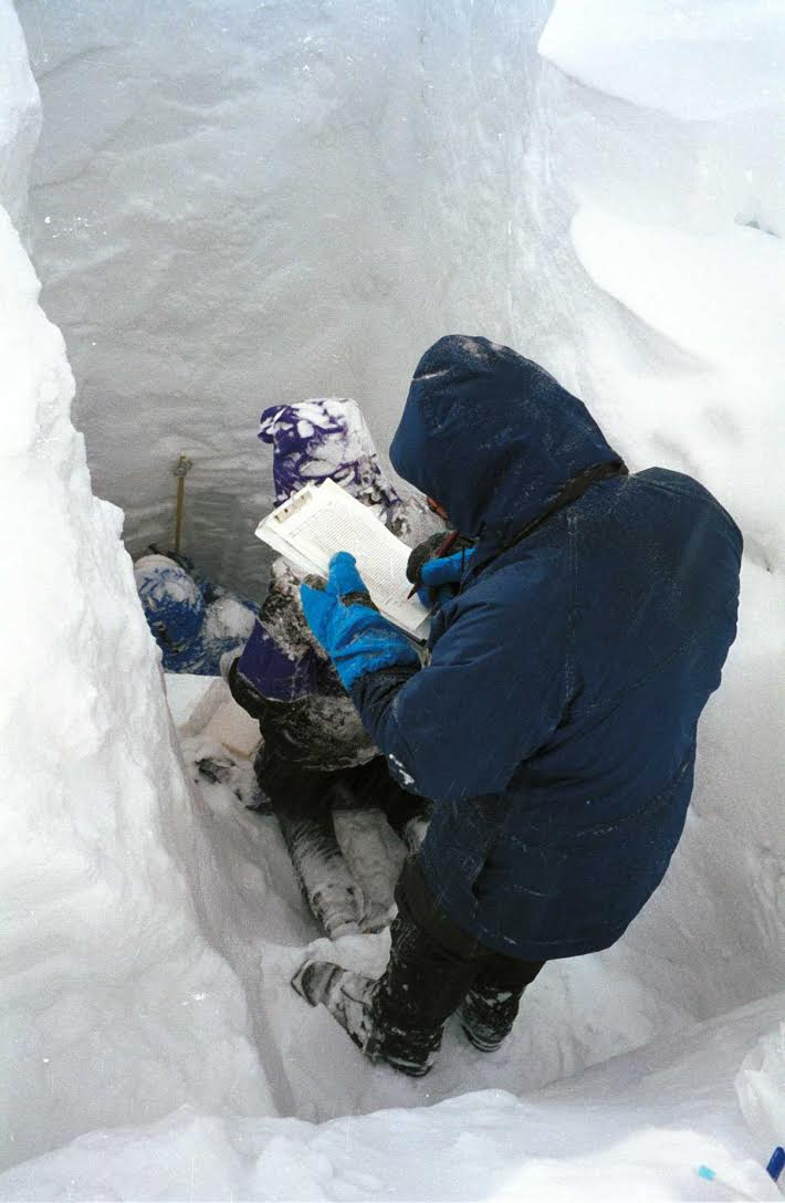 People recording measurements in a snowpack