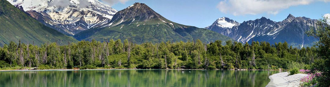 Sun is shining, the aqua green water is calm and the mountains of Lake Clark pristine.