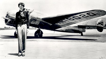 A tall woman stands in front of a plane
