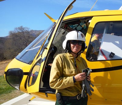 Woman pilot standing outside her helicopter