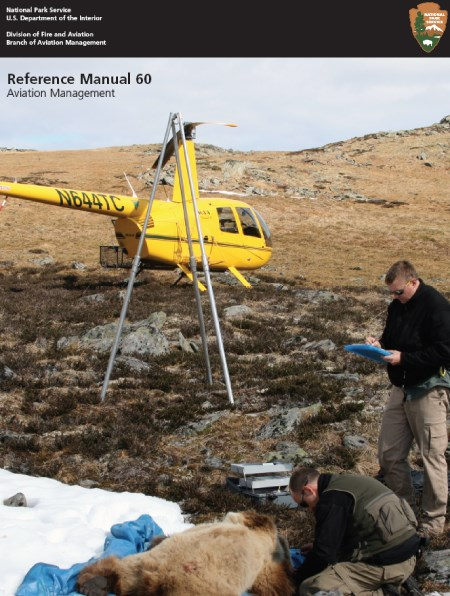 A yellow helicopter on a slope with two men standing over a prone bear
