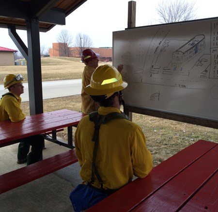 Three firefighters in yellow shirts and helmets sit in a pavillion