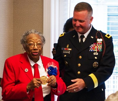 An older lady in a red coat holds up a gold medal while standing next to a man in a dark blue coat