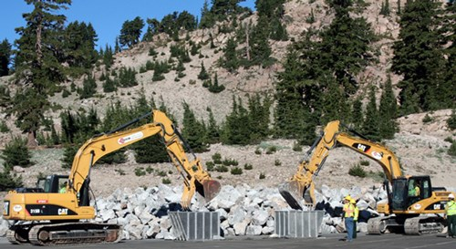 Two large yellow machines on the side of a large rock pile