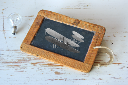 A chalk board with a plane drawing on it sitting next to a light bulb