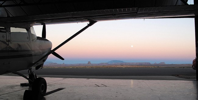 A plane sits in a dark hanger with a view of the sunset over the mountain range