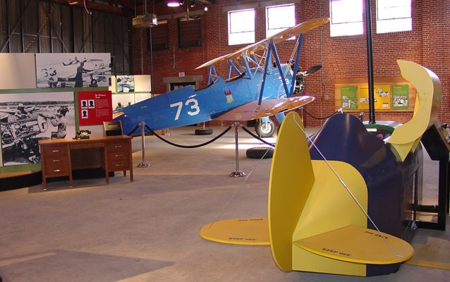 A blue airplane sits inside of a brick building