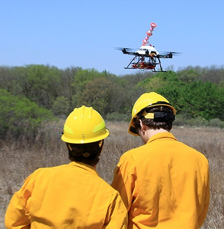 Two people in yellow helmets and shirts operate a drone aircraft above dry vegetation