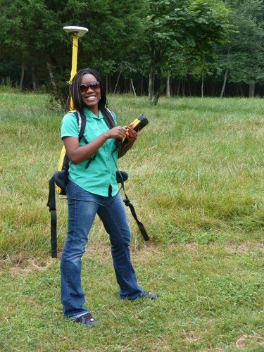 a young woman in jeans and green button up shirt stands in a grassy field with an antennae sticking up from a backpack and holds a scientific instrument in her hand.