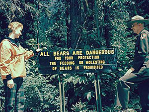 A visitor and a Ranger stand next to a bear warning sign in Glacier National Park, 1958