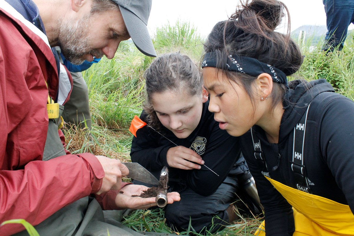 Archaeologist shows soil probe to two young girls at the summer camp