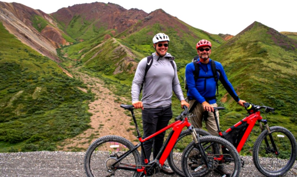 Two men pose with red bikes on treeless mountain trail